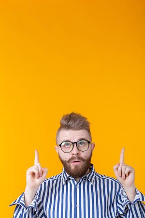 Solution is here. Handsome funny young man pointing copy space and looking up while standing against yellow background