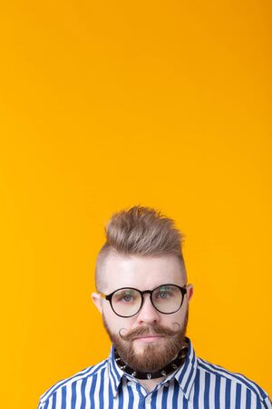 Young positive trendy man hipster with a mustache beard and necklace in shirt posing on a yellow background with copy space. Concept of rock and subculture. Vertical shot with copyspace