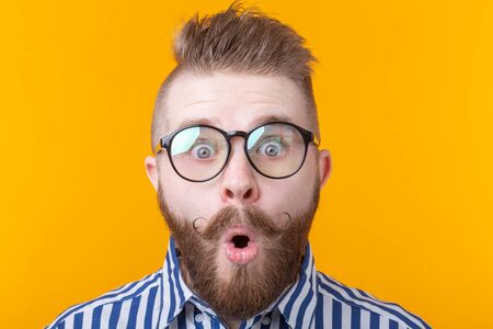 Young man with a mustache and beard rounded his mouth in surprise against a yellow background. Concept of surprise and uncertainty. Imagens