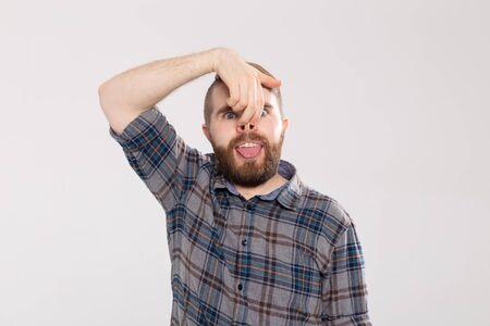 L'uomo bello mostra una smorfia sciocca pazza o un'espressione facciale, isolata su fondo bianco. Fare emozioni divertenti sul viso