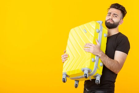 Happy young male hipster with a beard holding a yellow suitcase on a yellow background and rejoicing at a vacation. Travel and tourism concept. Banco de Imagens