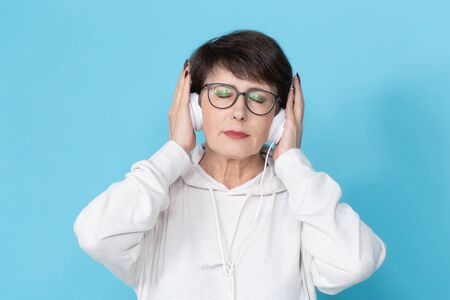 Middle-aged woman listening music on blue background.