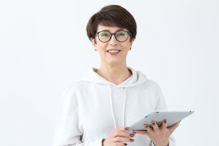 Cute middle-aged woman in casual clothes is looking online stores using a tablet on a white background. Concept of wireless internet and online shopping. Copyspace.