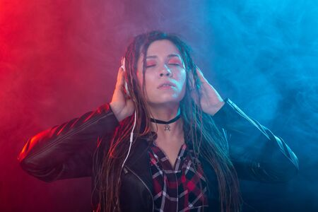 Music, meloman and people concept - A happy woman with dreadlock listening to music and enjoying it