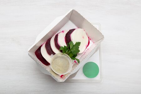 Top view of boiled beets with slices of white cheese lie in a white lunch box with sour cream sauce and parsley on a white table next to goat cheese. Protein snack concept.