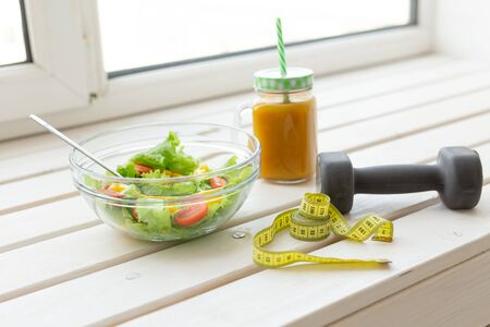 Vegetable salad and fruit smoothies and dumbbell lie on a white windowsill. Concept of healthy lifestyle physical activity and proper nutrition. 版權商用圖片
