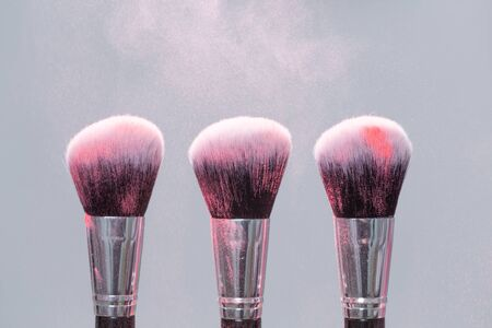 make up, beauty, mineral cosmetic concept - brush with pink powder over the light background Фото со стока