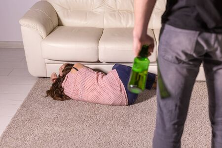 domestic violence, alcoholic and abuse concept - drunk man with bottle abusing his wife lying on the floor