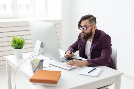 People and technology concept - Attractive man with beard, dressed in purple jacket working on at the computer