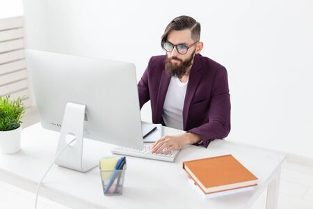 People and technology concept - Attractive man with beard working on at the computer