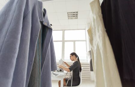 Tailor, people and seamstress concept - Low angle view of attractive young woman fashion designer working in studio