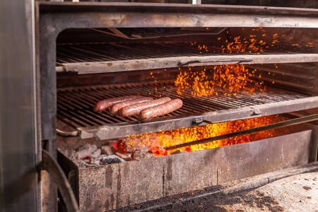 food, craft and delicious concept - cooking sausages on a grill Stock Photo