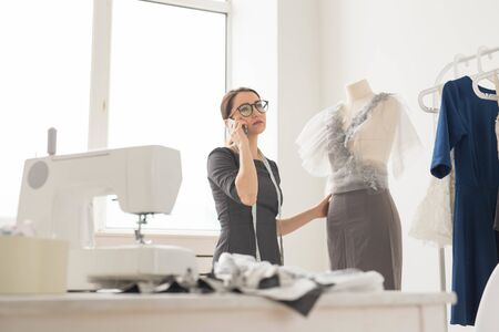 Dressmaker, tailor, fashion and showroom concept - beautiful young designer is talking on the mobile phone and smiling while examining her work in dressmaking studio Фото со стока