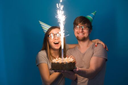 Funny nerd man and woman are wearing holidays caps and glasses holding birthday cake with candles over blue background