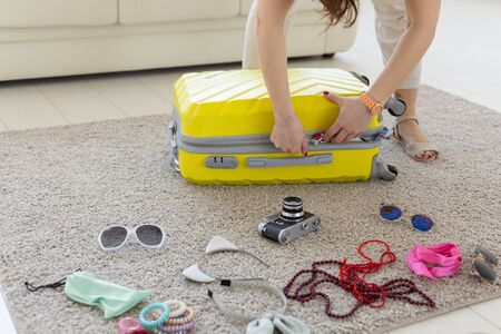 Vacation, travel and holidays concept - Woman trying to close suitcase with a lot of things. Imagens