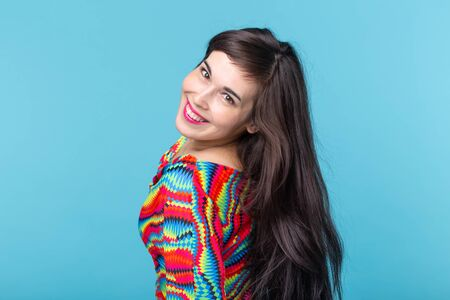 Cheerful young brunette woman with long hair posing on a blue background. The concept of a beautiful and well-groomed woman Stock fotó