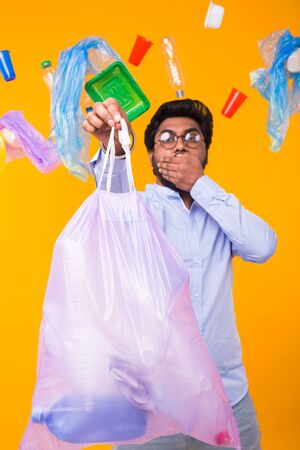 Environmental pollution, plastic recycling problem and waste disposal concept - scared man covering his mouth with hand. He is holding garbage bag on yellow background. Banque d'images