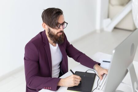 People and technology concept - Attractive man with beard, dressed in purple jacket working on at the computer Banque d'images