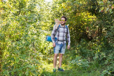 Adventures, summer tourism and nature concept - tourist arriving to a camping with his cat Stock Photo