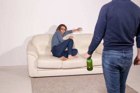 alcoholic, domestic violence and abuse concept - man gets drunk at home and takes his anger at his wife