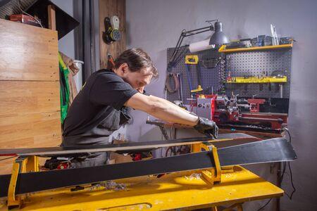 A man repairman in workshop ski service repairing the ski