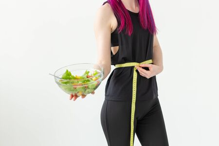 Young unidentified woman athlete with purple hair measures the waist of a measuring tape and holds a vegetable salad. Concept of proper nutrition and good shape