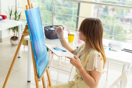 Art school, creativity and leisure concept - student girl or young woman artist with easel, palette and paint brush painting picture at studio Reklamní fotografie
