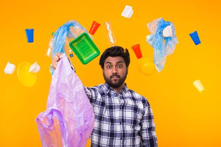 Environmental pollution, plastic recycling problem and waste disposal concept - surprised indian man holding garbage bag on yellow background.