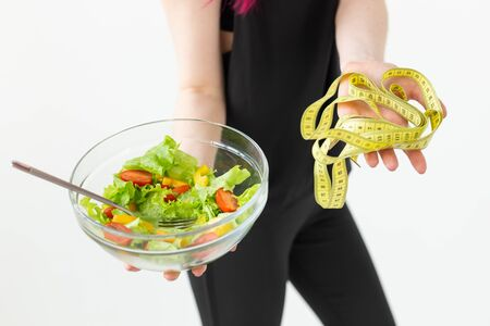 Young unidentified fitness blogger girl holding vegetable salad and measuring tape. Concept of sports lifestyle and proper nutrition.