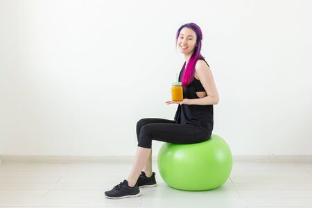 Cute young mixed race hipster girl with colored hair sitting on a green fitball and holding a banana protein smoothie in her hands on a white background. Healthy eating and exercise concept. Copyspace. Stock Photo
