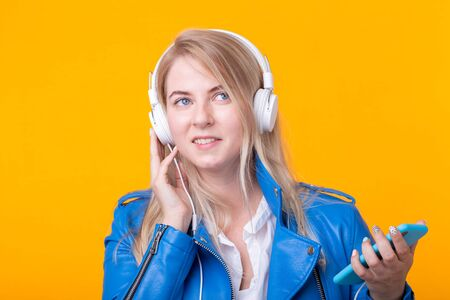 Portrait of pretty young girl blonde female student holding smartphone with blue leather jacket headphones posing on a yellow background. Concept of listening to online radio and music subscription.