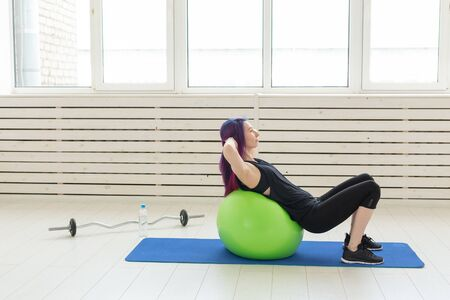 Young slim girl does exercise and stretching for the back on a green fitball In the bright gym. Healthy back and ligament concept.