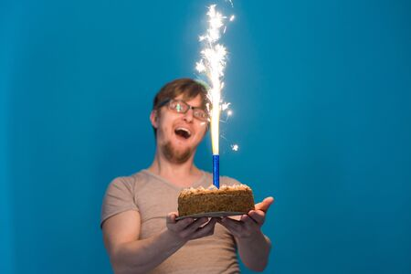 Crazy cheerful guy student in glasses greeting with a paper hat holding a cake with burning fireworks in his hands. Holiday birthday concept