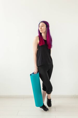 Slim young mixed race girl hipster with colored hair folds gymnastic mat after yoga in the gym. Healthy lifestyle and fitness concept. Stock Photo