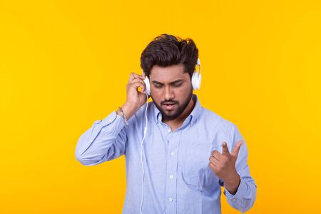 Positive young indian male listens to your favorite online radio using smartphone headphones and high-speed wireless internet on yellow background Stock Photo