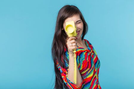 Portrait of a smiling young woman with a vintage yellow video camera in her hands posing against a blue background. Concept of video and photography
