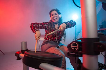 Emotions, music and hobby concept - young woman musician playing the electronic drum set