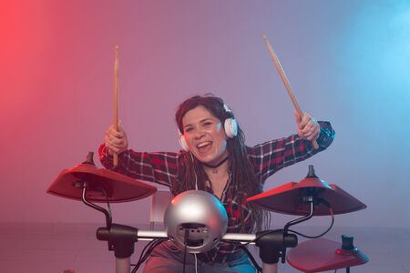 Music, drum and hobby concept - young woman playing the electronic drum set at the club Imagens