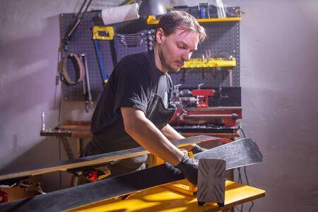 A man in work clothes repairman in the workshop ski service repairing the ski