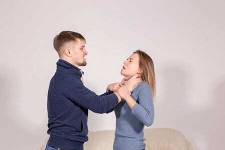 people, domestic violence and abuse concept - young man choked his wife on white background Imagens
