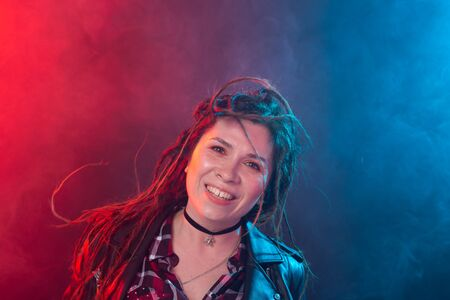 Portrait of young woman with dreadlocks having fun over the dark background