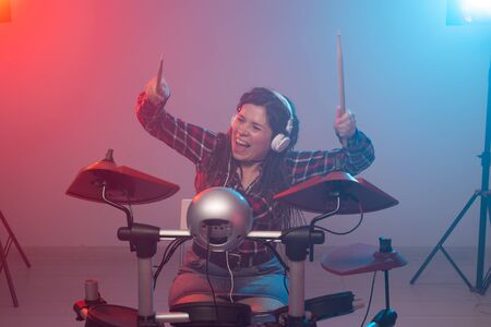 Hobby, music and people concept - Excited woman playing the electronic drum set Imagens