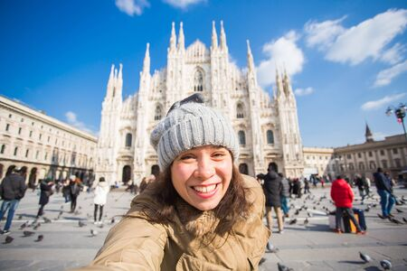 Winter travel, vacations and birds concept - Young funny woman taking selfie with pigeons near Milan Cathedral Duomo di Milano, Italy.