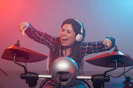 Emotions, music, hobbies and people concept - young woman playing the electronic drum set in studio