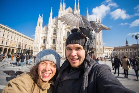 Travel, Italy and funny couple concept - Happy tourists taking a self portrait with pigeons in front of Duomo cathedral, Milan Banco de Imagens