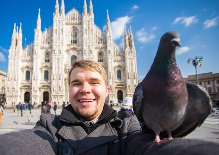 Winter travel, vacations and birds concept - Young funny man taking selfie with pigeons near Milan Cathedral Duomo di Milano, Italy. Banco de Imagens