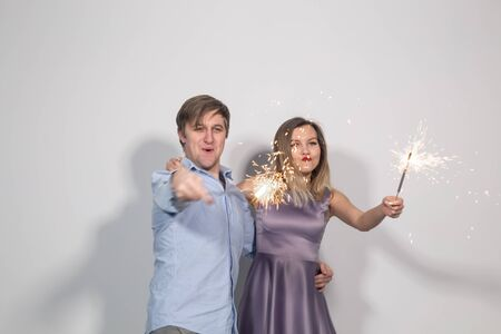 Party, fun and holidays concept - young happy couple with sparklers on white background Stock fotó