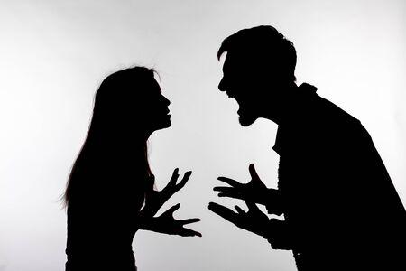 Relatieproblemen, conflict en misbruik concept - man en vrouw van aangezicht tot aangezicht schreeuwen schreeuwen elkaar geschil silhouet geïsoleerd op witte achtergrond Stockfoto
