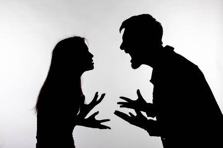 Relationship difficulties, conflict and abuse concept - man and woman face to face screaming shouting each other dispute silhouette isolated on white background