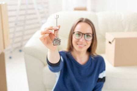 Moving, real estate and apartment purchase concept - Happy single woman apartment owner or renter showing keys and looking at you Standard-Bild